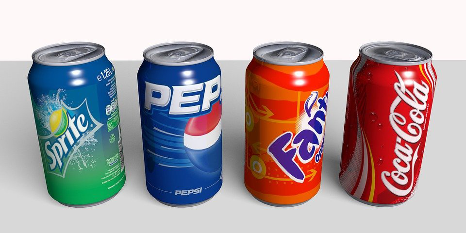 Four different soda cans and colors in a line.